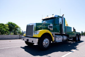69135909 - modern compact semi truck for transportation of broken semi trucks big rigs which need towing service, with all necessary equipment and tools with lifting winch moves on the wide highway